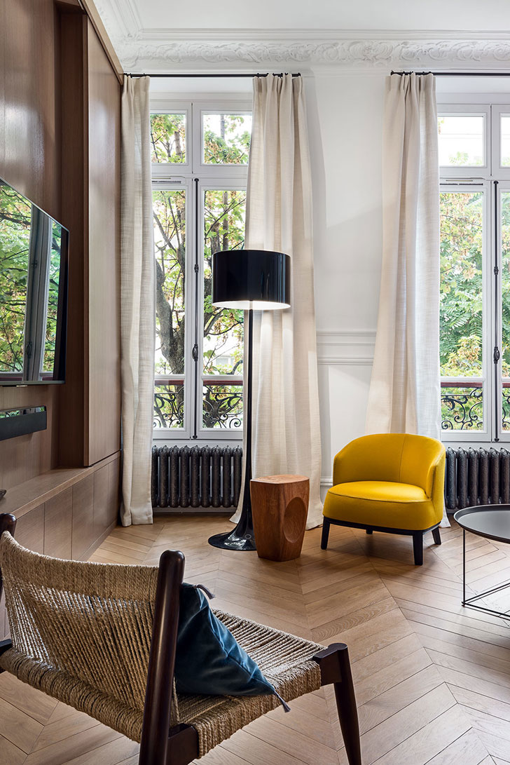 Contemporary living room with long windows, a yellow chair, a woven chair, a wooden side table, a black floor lamp, and wooden herringbone floor.