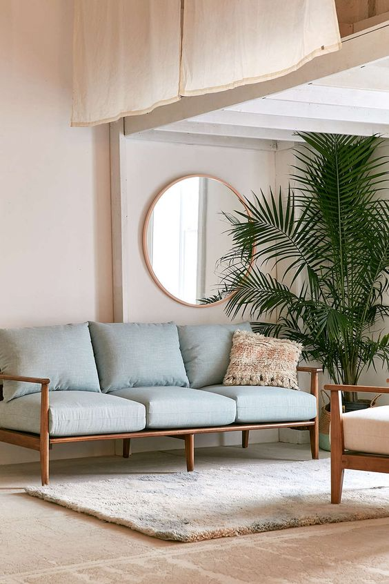 Minimalist living room with palm plant, circular wall mirror, and a light blue sofa with a wooden frame