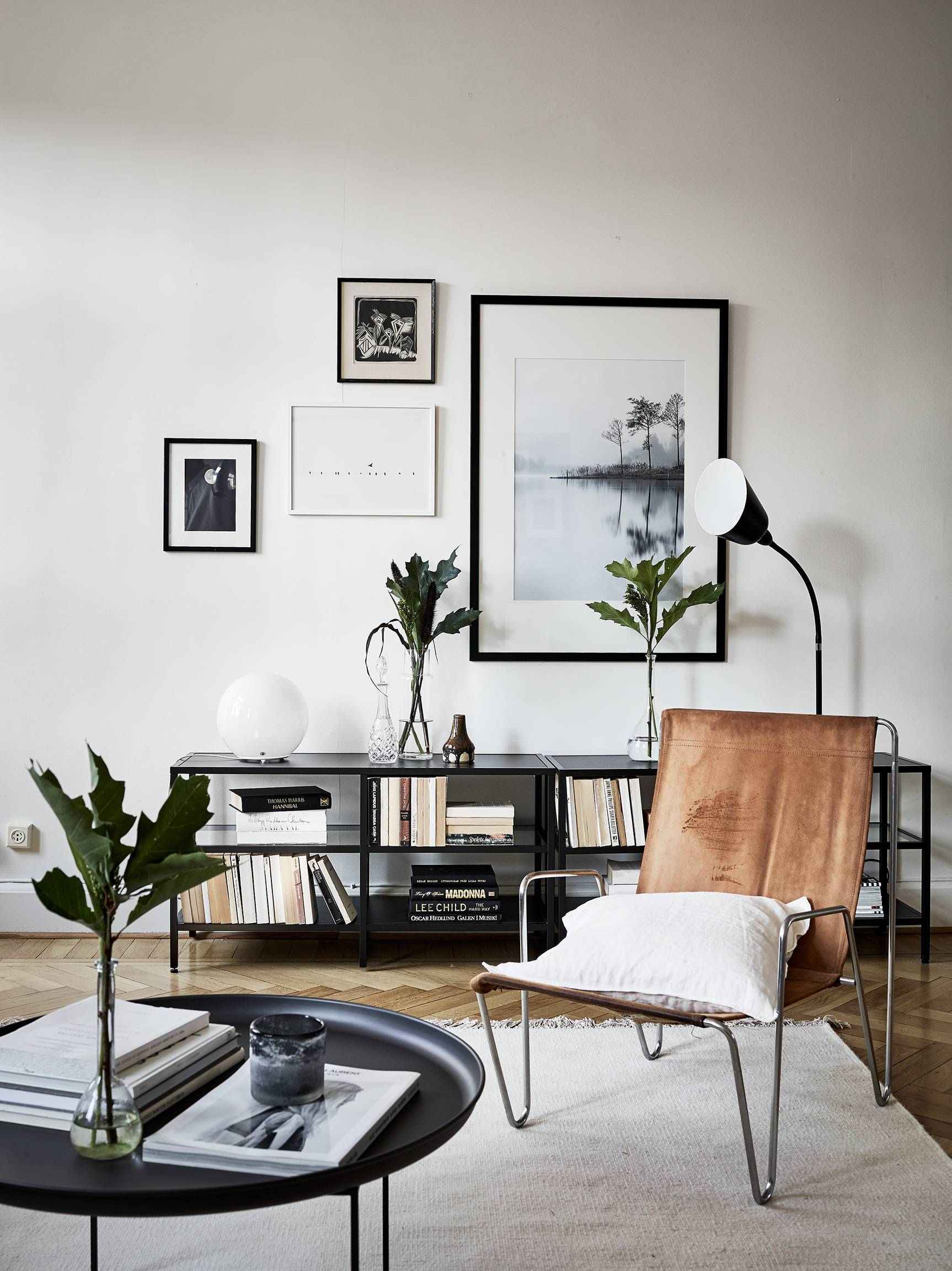 Room with table, chair, low book shelf, and wall art