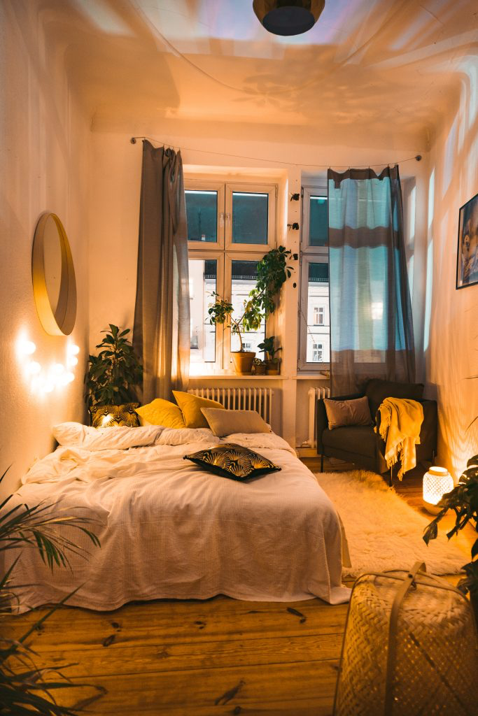Bohemian bedroom with white bed without headboard, window plants, and warm lighting from a small lamp on the floor and wall string lights.