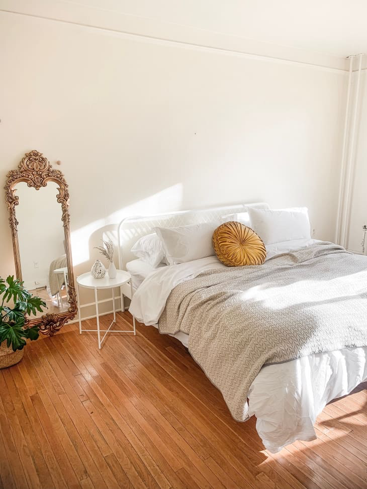 Minimalist boho bedroom with white bed, wooden floors, vintage full length mirror, plant and bedside table