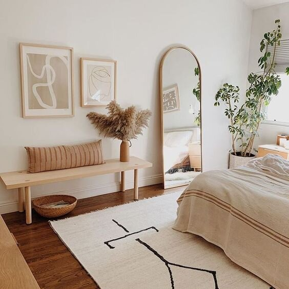 Bedroom decor with wooden bench, full length wall mirror, white rug, plants, and wall art.