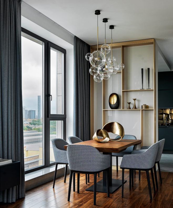 Modern dining room by windows, with wooden table and 6 grey chairs, featuring a golden sculpture on the table and bubble glass ceiling light