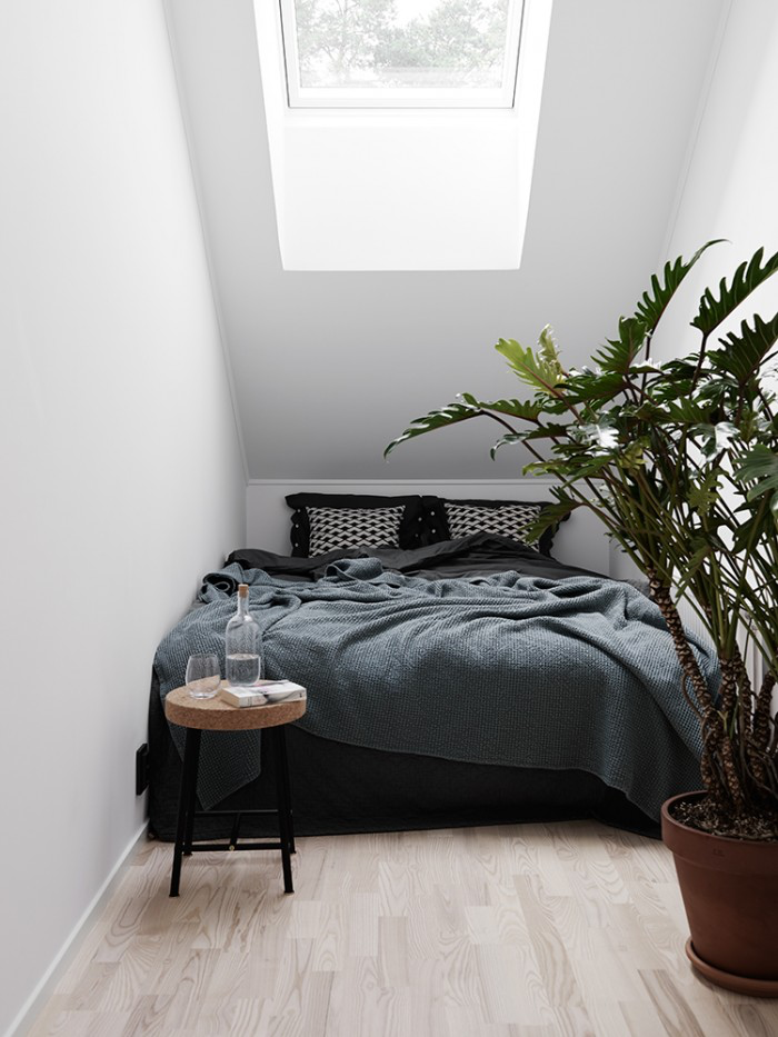 minimalistic bedroom with stool and plant