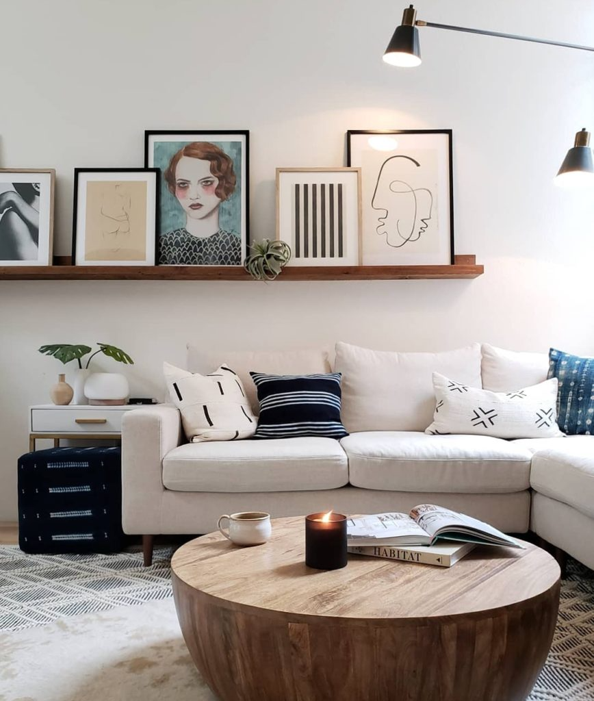 Living room with white sofa, circular wooden coffee table, and wall shelf with big framed art