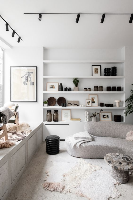 White carpeted living room corner with curved grey sofa, built in wall shelf, and animal fur rugs