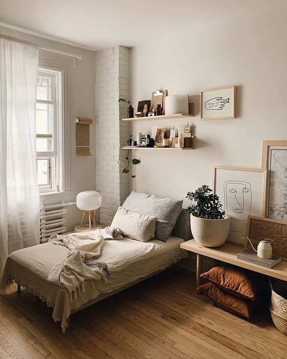 Nude palette bedroom with single bed, with wooden floors, wall shelf, bench, and framed art.